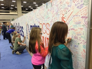 Taylor & Alli signing the banner.